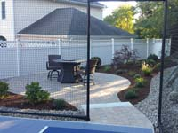 Backyard basketball court with landscaping, wall and patio, designed to maximize and enhance an awkward space in Stoneham, MA.