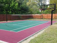 Residential combination tennis and basketball court in Sudbury, MA, in red and green Versacourt tiles.