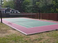 Red and green home court in Sudbury, MA, primarily lined for tennis and secondarily lined for basketball. Tennis net is adjustable and removable.