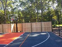 Graphite and orange residential basketball court in Walpole, MA, featuring custom cedar and rebound fence.