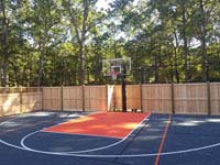 Finished picture of bulk of charcoal and orange home basketball court, looking toward hoop, showing part of custom fence that incorporates traditional cedar wood with rebounder mesh segments, in Walpole, MA.