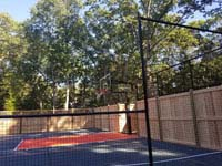 Looking through mesh court fence at hoop end of graphite and orange home basketball court in Walpole, MA, including custom fencing that combines cedar fence with a topper of mesh.