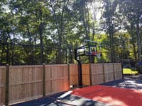 Graphite and orange residential basketball court in Walpole, MA, highlighting goal and custom fencing combining cedar and more traditional court containment fence. Also visible, a section of rebound fence without the wooden portion.