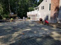 Pouring reinforced concrete base for graphite and orange backyard basketball court replacing a dead pool in Walpole, MA.
