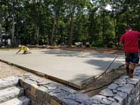Grooming cement base for graphite and orange residential basketball court replacing a dead pool in Walpole, MA.