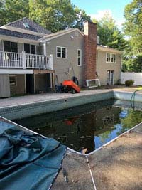 Dead pool that will be replaced be a graphite and orange basketball court in Walpole, MA.