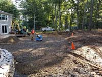 Preparing and packing ground to put in a base for graphite and orange residential basketball court replacing a dead pool in Walpole, MA.