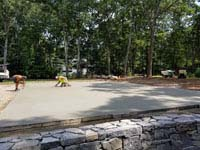 Preparing cement base for graphite and orange residential basketball court replacing a dead pool in Walpole, MA.