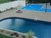 Light blue and grey basketball court integrated with pool deck in Wareham, MA, also featuring shuffleboard.