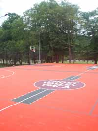 Surfaced giant multiple basketball court at Frost Valley YMCA in Claryville, NY. Features orange, black and burgundy tiles, plus custom logos.