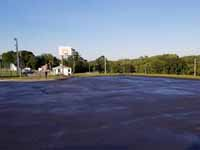Modern resurfacing of decrepit town basketball court in Middleboro, MA for tennis and pickleball, blue and green with portable net. Almost complete sealcoating of the old asphalt after other work has been done, last step before tile surface.