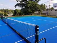 Modern resurfacing of decrepit town basketball court in Middleboro, MA for tennis and pickleball, blue and green with portable net.