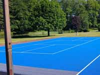 Resurfaced municipal basketball courts in Walpole, NH to create a combo of pickleball and basketball on comfortable, durable royal blue and graphite versacourt tile.