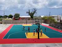 Replacement tennis and basketball courts in Codrington, Barbuda, courtest of Australia, the Red Cross, and community effort, part of the ongoing recovery from hurricane Irma. Shown here, people trying out the new basketball surface and goals.