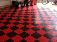 Example picture of an installation of specialty indoor tile floor in a garage, in alternating red and black.